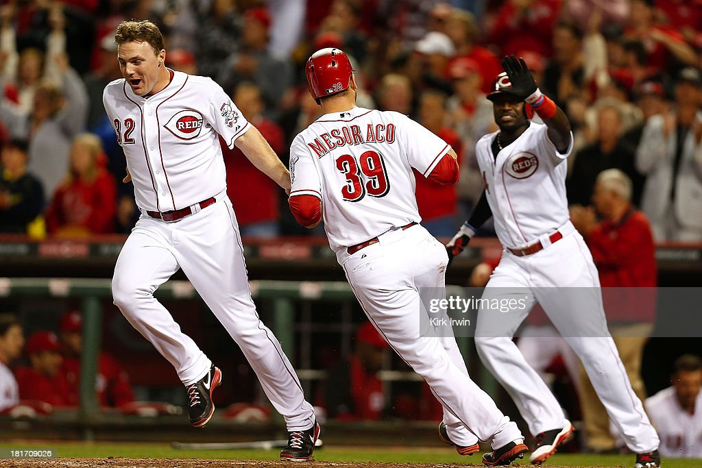 <a gi-track='captionPersonalityLinkClicked' href=/galleries/search?phrase=Devin+Mesoraco&family=editorial&specificpeople=5745587 ng-click='$event.stopPropagation()'>Devin Mesoraco</a> #39 is congratulated by <a gi-track='captionPersonalityLinkClicked' href=/galleries/search?phrase=Jay+Bruce&family=editorial&specificpeople=4391540 ng-click='$event.stopPropagation()'>Jay Bruce</a> #32 and Brandon Phillips #4 of the Cincinnati Reds after scoring the winning run during the 10th inning against the New York Mets at Great American Ball Park on September 23, 2013 in Cincinnati, Ohio. Cincinnati defeated New York 3-2 in 10 innings.