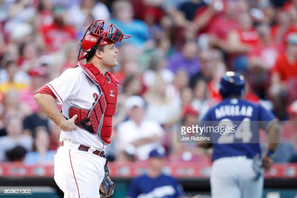 Devin Mesoraco of the Cincinnati Reds reacts after dropping the ball and allowing Jesus Aguilar of the Milwaukee Brewers to score in the third inning...