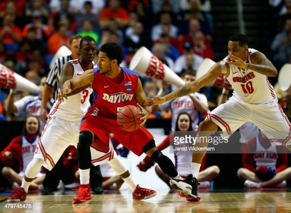 Devin Oliver of the Dayton Flyers controls the ball as LaQuinton Ross and Shannon Scott of the Ohio State Buckeyes defend during the second round of...