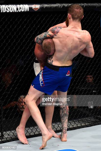 Devin Powell attempts to secure a guillotine choke submission against Darrell Horcher in their lightweight bout during the UFC Fight Night event at...