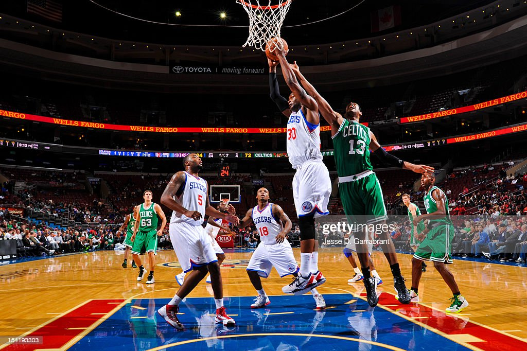 Devin Searcy #30 of the Philadelphia 76ers grabs a rebound against Fab Melo #13 of the Boston Celtics during a pre-season game at the Wells Fargo Center on October 15, 2012 in Philadelphia, Pennsylvania.