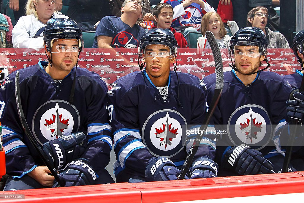 Devin Setoguchi #40, Evander Kane #9 and Michael Frolik #67 of the Winnipeg Jets look on from the bench prior to puck drop against the Dallas Stars at the MTS Centre on October 11, 2013 in Winnipeg, Manitoba, Canada.