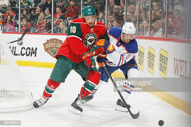 Devin Setoguchi of the Minnesota Wild and Eric Belanger of the Edmonton Oilers battle for a loose puck during the game on March 3 2013 at the Xcel...
