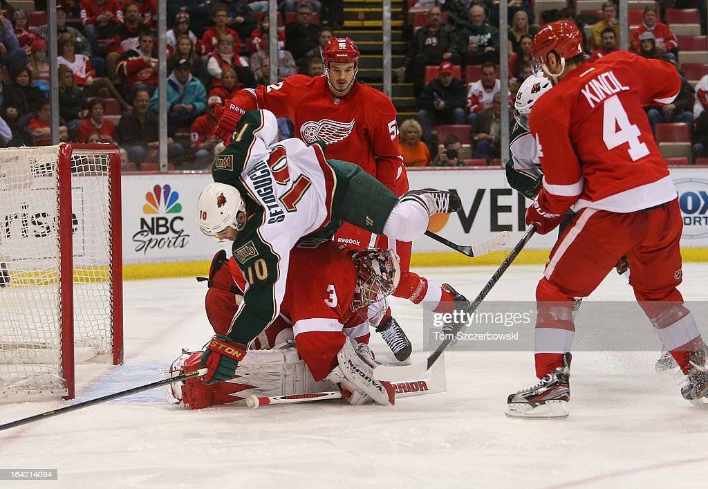Devin Setoguchi #10 of the Minnesota Wild collides with goalie Jimmy Howard #35 of the Detroit Red Wings in NHL action at Joe Louis Arena on March 20, 2013 in Detroit, Michigan.