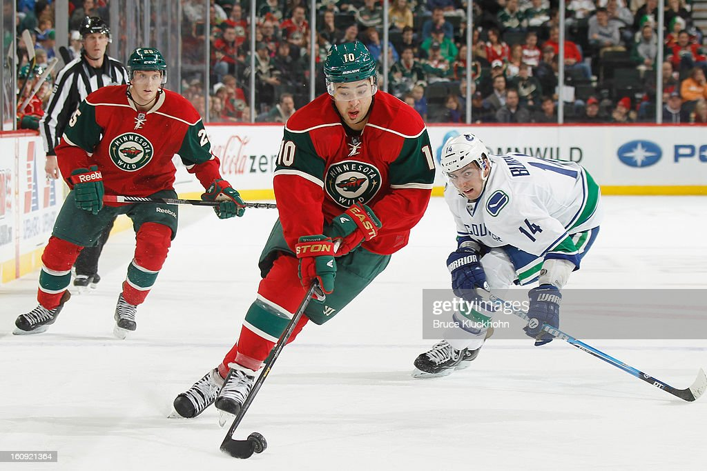 Devin Setoguchi #10 of the Minnesota Wild skates with the puck while Alex Burrows #14 of the Vancouver Canucks gives chase during the game on February 7, 2013 at the Xcel Energy Center in St. Paul, Minnesota.