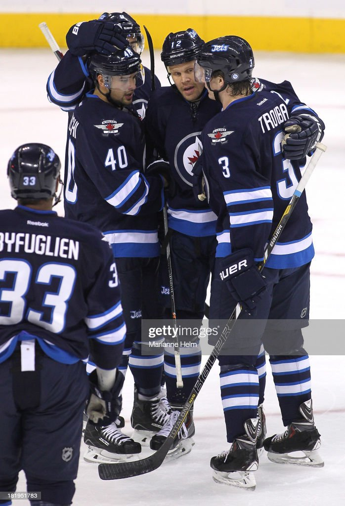 Devin Setoguchi #40 of the Winnipeg Jets is congratulated by teammates Olli Jokinen #12 and Jacob Trouba #3 for his first preseason goal in first period action during an NHL preseason game at the MTS Centre on September 26, 2013 in Winnipeg, Manitoba, Canada.