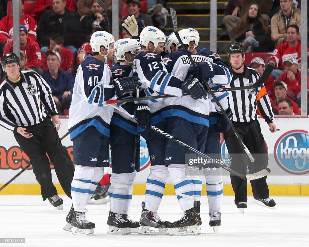 Devin Setoguchi #40, Tobias Enstrom #39, Olli Jokinen #12 and Evander Kane #9 of the Winnipeg Jets surround teammate Zach Bogosian #44 after scoring a third period goal during an NHL game against the Detroit Red Wings at Joe Louis Arena on November 12, 2013 in Detroit, Michigan.