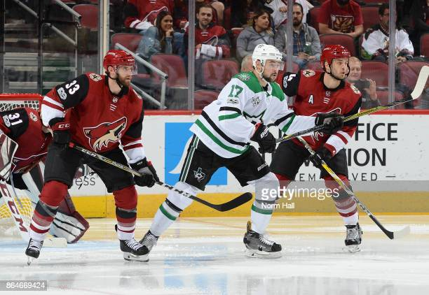 Devin Shore of the Dallas Stars battles for position with Alex Goligoski and Niklas Hjalmarsson of the Arizona Coyotes at Gila River Arena on October...