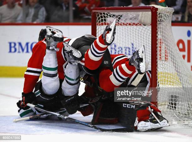 Devin Shore of the Dallas Stars colides with Corey Crawford and Trevor van Riemsdyk of the Chicago Blackhawks at the United Center on March 23 2017...