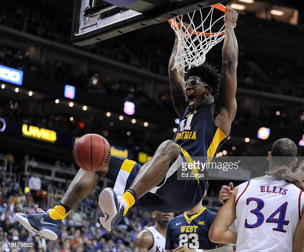 Devin Williams of the West Virginia Mountaineers dunks against Perry Ellis of the Kansas Jayhawks in the first half during the championship game of...