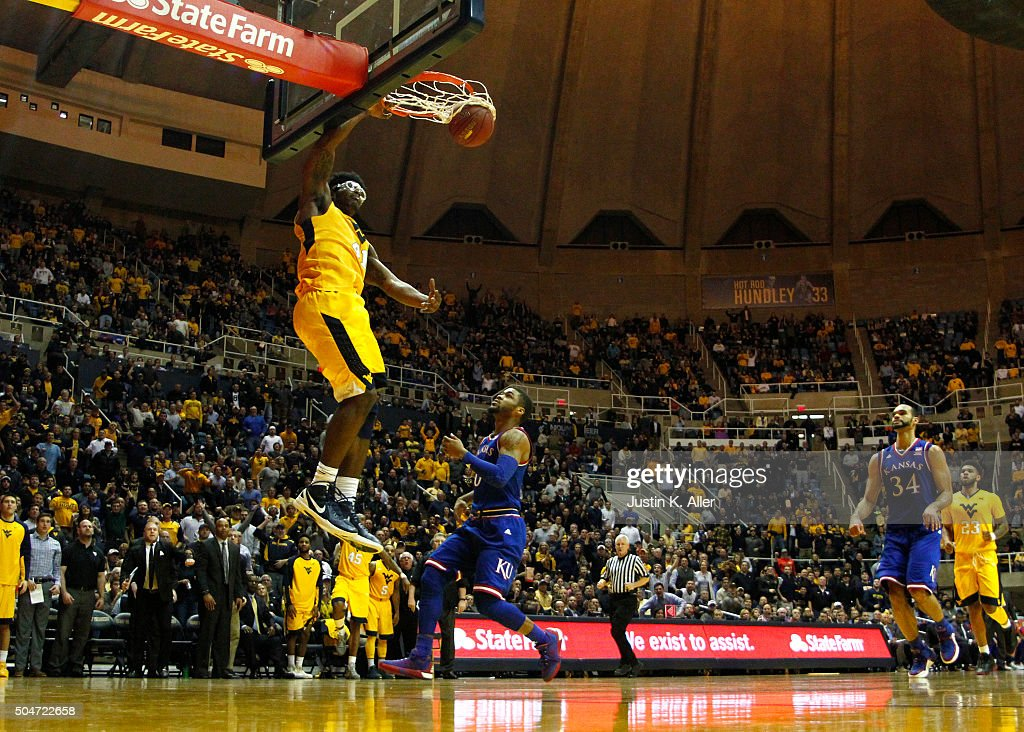 Devin Williams of the West Virginia Mountaineers dunks the ball against Frank Mason III of the Kansas Jayhawks during the game at the WVU Coliseum on...