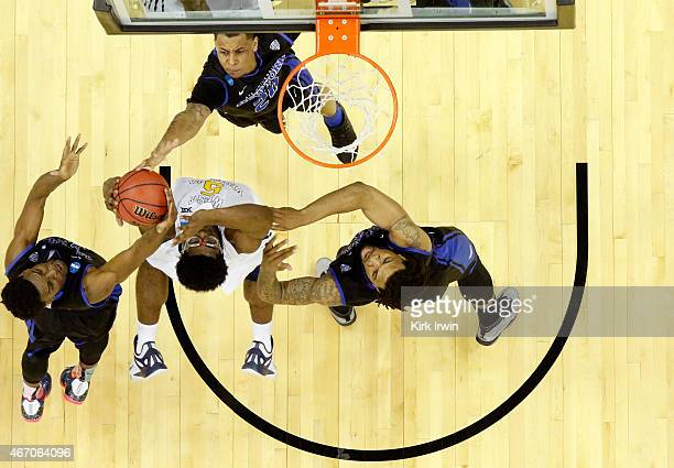 Devin Williams of the West Virginia Mountaineers fights for the ball with Xavier Ford Rodell Wigginton and Justin Moss of the Buffalo Bulls in the...
