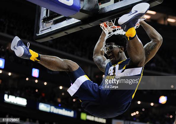 Devin Williams of the West Virginia Mountaineers hangs on the rim after dunking against the Kansas Jayhawks in the first half during the championship...