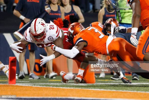 Devine Ozigbo of the Nebraska Cornhuskers dives for the touchdown as Del'Shawn Phillips of the Illinois Fighting Illini tries to make the stop at...