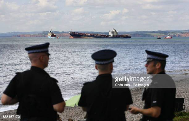 Devon and Cornwall Police officers look on from Branscombe beach to the stricken container ship MSC Napoli Salvage workers will use explosive devices...