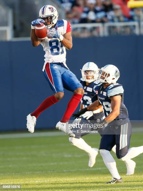 Devon Bailey of the Montreal Alouettes goes airborne to make a catch against Matt Black and Robert Woodson of the Toronto Argonauts during a CFL...