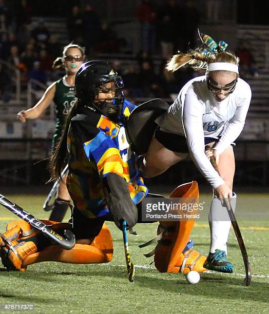 Devon Datsis of York is tripped up by Spruce Mountain goalie Grace Ryan during the second half of the Class B Field Hockey Regional Championship
