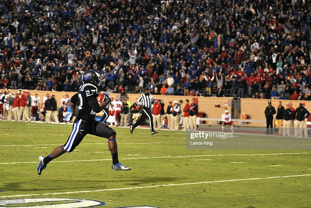 DeVon Edwards #27 of the Duke Blue Devils runs for a touchdown on a 100-yard kickoff return against the North Carolina State Wolfpack at Wallace Wade Stadium on November 9, 2013 in Durham, North Carolina. Duke defeated NC State 38-20.