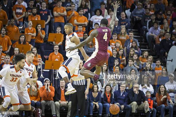 Devon Hall of the Virginia Cavaliers blocks Dwayne Bacon of the Florida State Seminoles during a game at John Paul Jones Arena on December 31 2016 in...