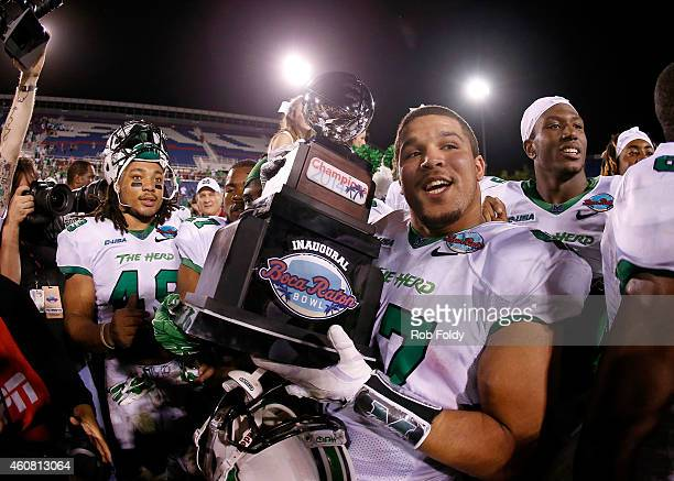 Devon Johnson of the Marshall Thundering Herd holds the championship trophy after the game against the Northern Illinois Huskies at FAU Stadium on...