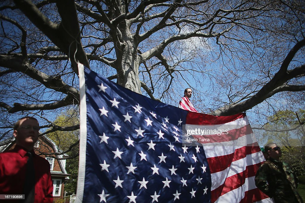 Devon Morancie (TOP) sits on a tree branch while wearing an American flag outside the funeral for 29-year-old Krystle Campbell, who was one of three people killed in the Boston Marathon bombings, on April 22, 2013 in Medford, Massachusetts. The 29-year-old restaurant manager was raised in Medford. Massachusetts Gov. Deval Patrick has asked residents to observe a moment of silence at the time of the first explosion at 2:50 p.m. this afternoon.