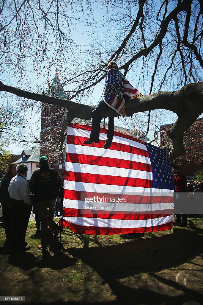 Devon Morancie sits on a tree branch while wearing an American flag outside the funeral for 29-year-old Krystle Campbell, who was one of three people killed in the Boston Marathon bombings, on April 22, 2013 in Medford, Massachusetts. The 29-year-old restaurant manager was raised in Medford. Massachusetts Gov. Deval Patrick has asked residents to observe a moment of silence at the time of the first explosion at 2:50 p.m. this afternoon.