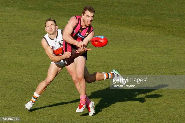 Devon Smith of the Giants tackles Tom Mitchell of the Hawks during the round 16 AFL match between the Hawthorn Hawks and the Greater Western Sydney...