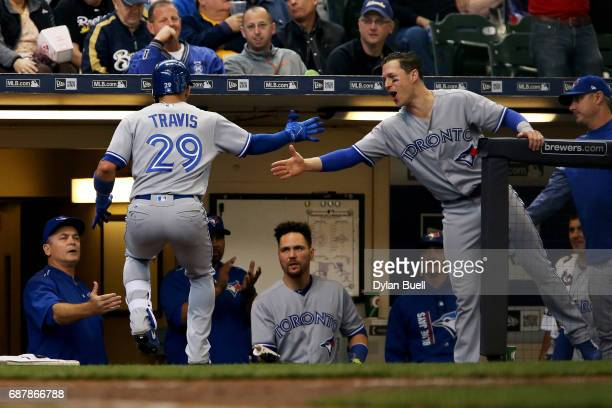 Devon Travis and Chris Coghlan of the Toronto Blue Jays celebrate after Travis hit a home run in the sixth inning against the Milwaukee Brewers at...