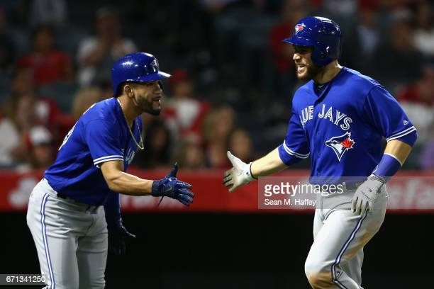 Devon Travis congratulates Russell Martin after scoring on a tworun double hit by Justin Smoak of the Toronto Blue Jays during the eighth inning of a...