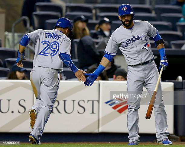 Devon Travis is congratulated by teammate Jose Bautista of the Toronto Blue Jays after Travis scored in the fifth inning against the New York Yankees...