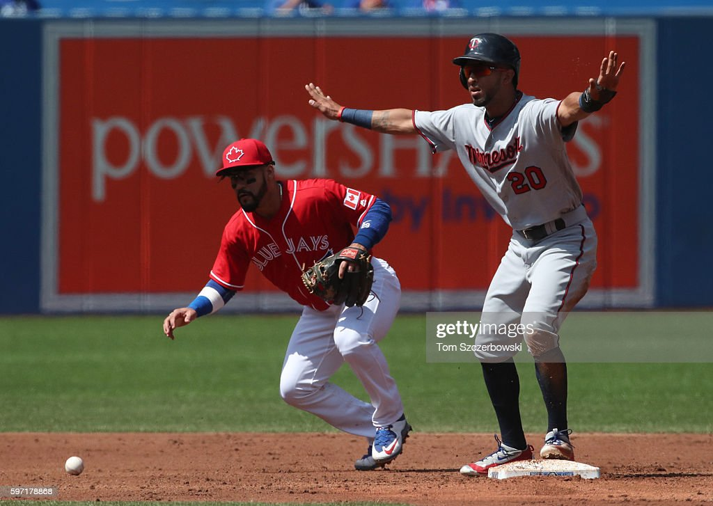 Devon Travis of the Toronto Blue Jays cannot handle a throwing error from Josh Donaldson as Eddie Rosario of the Minnesota Twins arrives at second...