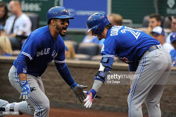Devon Travis of the Toronto Blue Jays celebrates his home run with Josh Donaldson in the first inning against the Kansas City Royals at Kauffman...
