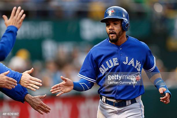 Devon Travis of the Toronto Blue Jays celebrates scoring a run in the third inning against the Oakland Athletics at Oco Coliseum on July 22 2015 in...