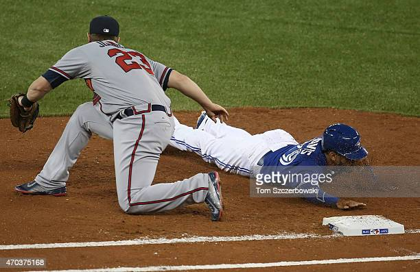 Devon Travis of the Toronto Blue Jays dives back to first base in the first inning during MLB game action against the Atlanta Braves on April 19 2015...