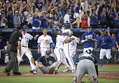 Devon Travis of the Toronto Blue Jays is congratulated by Edwin Encarnacion as Kevin Pillar leaps in the air after their gamewinning run scored on a...