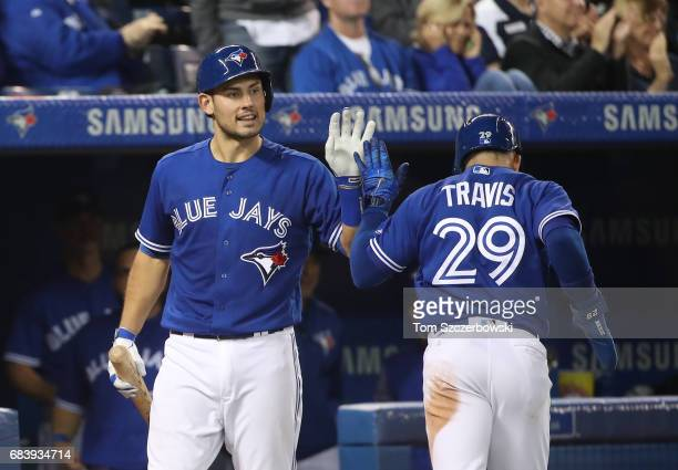 Devon Travis of the Toronto Blue Jays is congratulated by Luke Maile after scoring the tying run in the sixth inning during MLB game action against...