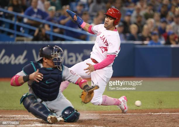 Devon Travis of the Toronto Blue Jays steals home plate in the eighth inning during MLB game action as Carlos Ruiz of the Seattle Mariners tries to...