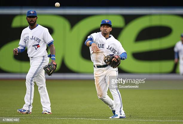 Devon Travis of the Toronto Blue Jays throws out the baserunner as Jose Reyes watches in the fifth inning during MLB game action against the Texas...