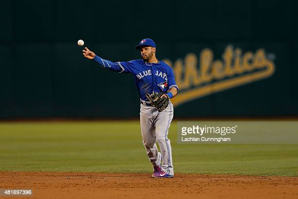 Devon Travis of the Toronto Blue Jays throws to first base to get the out of Ben Zobrist of the Oakland Athletics in the third inning at Oco Coliseum...