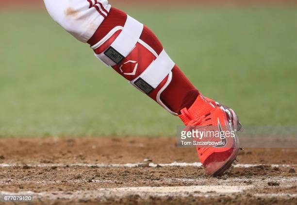 Devon Travis of the Toronto Blue Jays wears bright red Nike cleats and a shin guard as he bats in the eighth inning during MLB game action against...