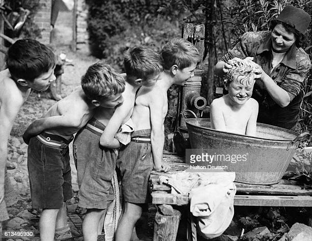 A Devonshire farmer's wife scrubs the hair of one of her young evacuee helpers after a stint in the potato fields England August 1941