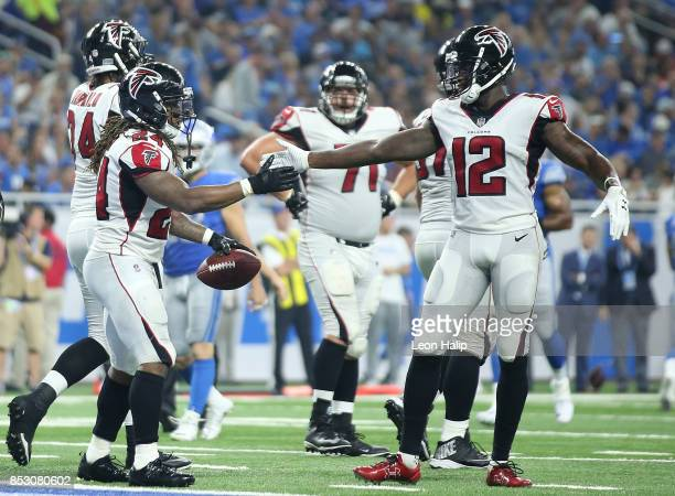 Devonta Freeman of the Atlanta Falcons celebrates a second quarter touchdown with teammate Mohamed Sanu during the game against the Detroit Lions at...