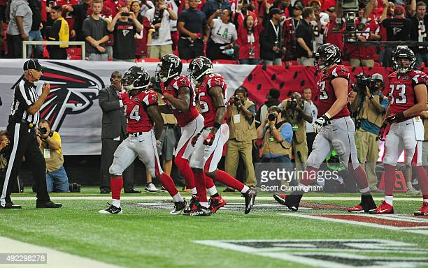 Devonta Freeman of the Atlanta Falcons celebrates with teammates after scoring against the Washington Redskins at the Georgia Dome on October 11 2015...