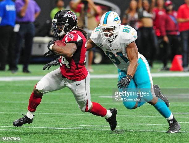 Devonta Freeman of the Atlanta Falcons is pursued by Cameron Wake of the Miami Dolphins at MercedesBenz Stadium on October 15 2017 in Atlanta Georgia