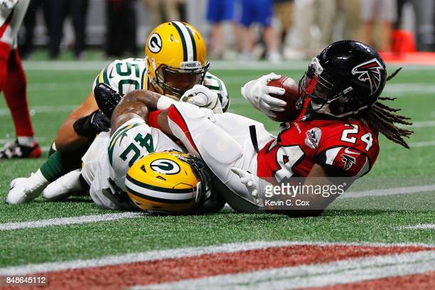 Devonta Freeman of the Atlanta Falcons scores a 1yard rushing touchdown during the first quarter against the Green Bay Packers at MercedesBenz...