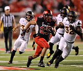 Devontae Booker of the Utah Utes runs past Antonio Longino of the Arizona State Sun Devils for a fourth quarter touchdown in their game at RiceEccles...