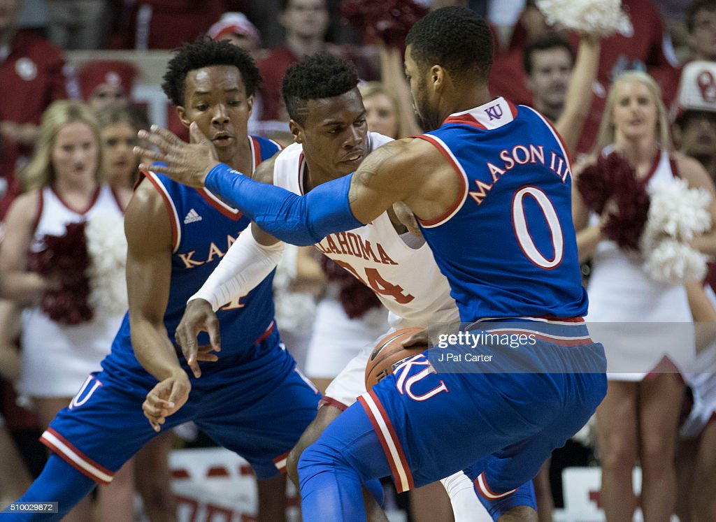 Devonte' Graham #4 of the Kansas Jayhawks and Sviatoslav Mykhailiuk #10 of the Kansas Jayhawks trap <a gi-track='captionPersonalityLinkClicked' href=/galleries/search?phrase=Buddy+Hield&family=editorial&specificpeople=9988395 ng-click='$event.stopPropagation()'>Buddy Hield</a> #24 of the Oklahoma Sooners as he looks for a play during the first half of a NCAA college basketball game at the Lloyd Noble Center on February 13, 2016 in Norman, Oklahoma.