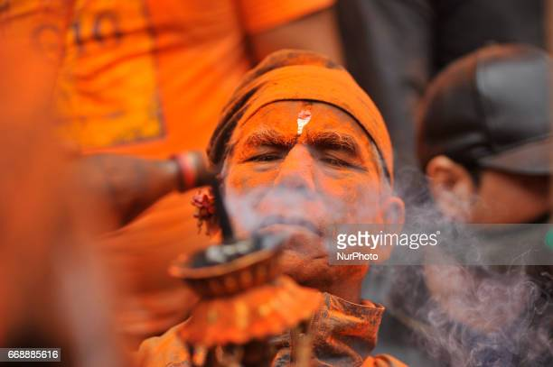 A devotee add oil on torch frame during the celebration of quotSindoor Jatraquot vermillion powder festival or Nepalese New Year day celebration at...