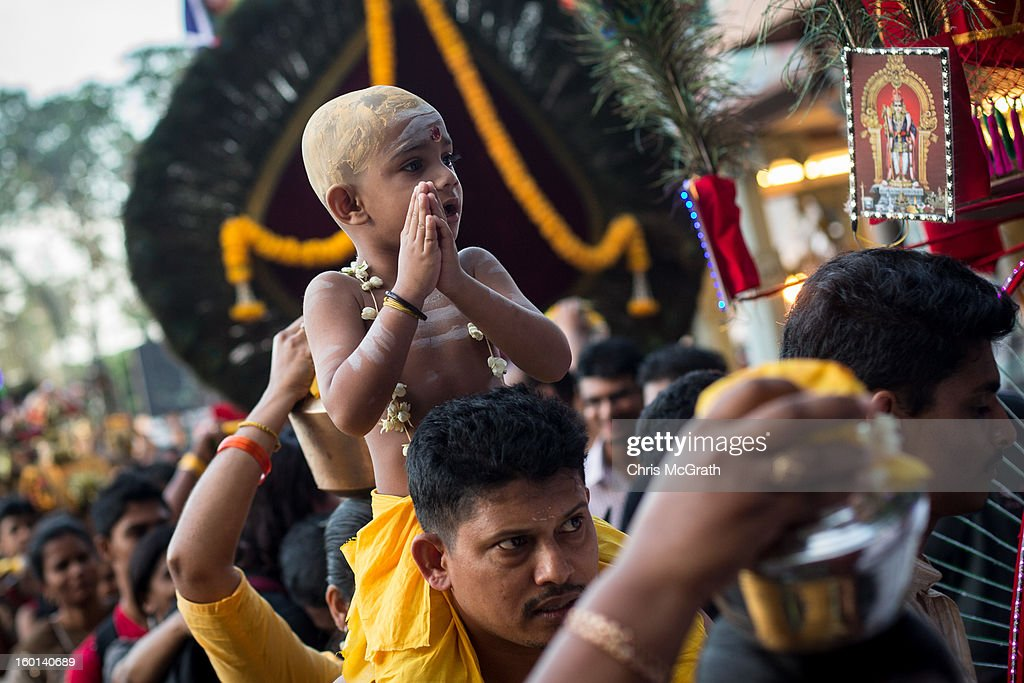 A devotee carries his child on his shoulders as he walks towards the entrance of the Batu Caves during the Thaipusam procession on January 27, 2013 in Batu Caves, Malaysia. Thaipusam is a Hindu festival celebrated on the full moon in the Tamil month of Thai. The festival marks the birthday of Lord Muruga and also commemorates the day Hindu Goddess Parvati gave her son a lance to defeat the evil demon Soorapadamwhen. The festival sees devotees carry milk pots to seek forgivness and some will carry a 'Kavadi' many of which are attached via, strings, hooks, and skews pierced into the carriers skin.