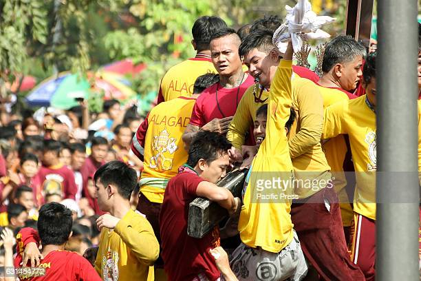 AVE MANILA NCR PHILIPPINES A devotee cheers wildly after being able to kiss the cross of the miraculous Icon of the Black Nazarene while another...
